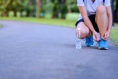donna dell'atleta che lega le scarpe da corsa nel parco all'aperto fotografie stock