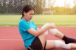 Donna dell'atleta che soffre dal dolore in gambe con la ferita al ginocchio dopo pareggiare e l'allenamento di funzionamento di e immagine stock