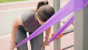 Donna dell'atleta che utilizza l'estensore di sport per l'addestramento all'aperto di forma fisica nel parco di estate archivi video
