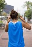 Donna dell'atleta giù alle cuffie prima dell'esercitazione, all'aperto immagini stock