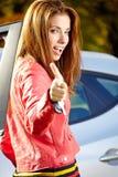 Donna dell'autista di automobile che mostra le nuove chiavi dell'automobile ed automobile. Fotografie Stock Libere da Diritti