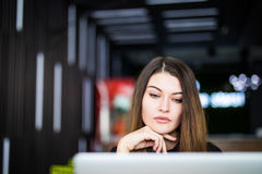 Donna dell'imprenditore che lavora con un computer portatile in uno spazio astuto del hub o della caffetteria Fotografia Stock