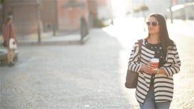 Donna dell'imprenditore che parla sul telefono cellulare che si siede su un banco nella via con le costruzioni nei precedenti archivi video