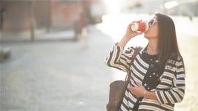 Donna dell'imprenditore che parla sul telefono cellulare che si siede su un banco nella via con le costruzioni nei precedenti stock footage