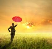 Donna dell'ombrello di affari che si leva in piedi al tramonto Fotografie Stock