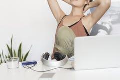 Donna dell'ufficio che si siede sulla sedia che la allunga braccioli Fotografie Stock