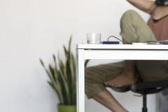 Donna dell'ufficio che si siede sulla sedia che la allunga braccioli Fotografie Stock Libere da Diritti
