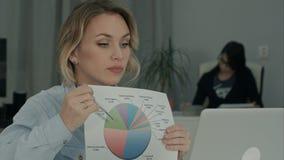 Donna dell'ufficio che spiega diagramma a torta ai colleghi tramite computer portatile immagine stock