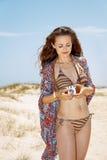 Donna della Boemia sulla spiaggia bianca che regola la retro macchina fotografica della foto Fotografie Stock Libere da Diritti
