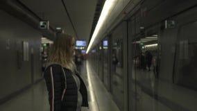 Donna della città sul treno in attesa della stazione della metropolitana sul binario Giovane donna del viaggiatore in metropolita stock footage