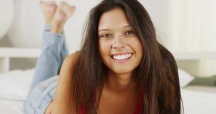 Donna della corsa mista che si trova sul letto che sorride alla macchina fotografica Fotografia Stock