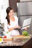 Donna della cucina sul computer portatile Fotografie Stock
