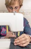 Donna della cucitrice di Senion che lavora alla macchina per cucire fotografie stock