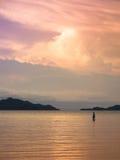 Donna della gioventù che esamina tramonto sul mare Fotografia Stock Libera da Diritti