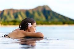 Donna della località di soggiorno dello stagno di infinito che si rilassa alla spiaggia Fotografia Stock