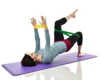 Donna della madre che si esercita facendo allenamento postnatale L'istruttore femminile di forma fisica tiene le gambe in palestr Immagine Stock
