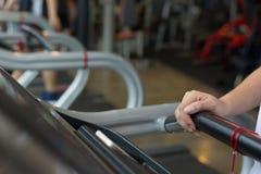 Donna della mano del primo piano che pareggia e che corre sulla pedana mobile cardio Fotografia Stock