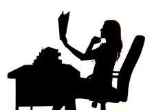 Donna della siluetta al libro dello scrittorio su che pensa Immagini Stock Libere da Diritti