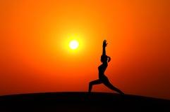 Donna della siluetta che fa yoga Immagini Stock