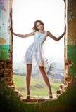 Donna della siluetta che si leva in piedi alla finestra Fotografia Stock