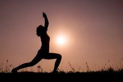 Donna della siluetta con yoga di posizione diritta fotografia stock libera da diritti