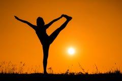 Donna della siluetta con yoga di posizione diritta Immagini Stock