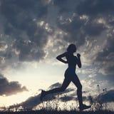 Donna della siluetta fatta funzionare sotto cielo blu con le nuvole Fotografia Stock Libera da Diritti