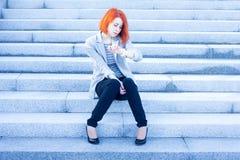 Donna della testarossa che si siede fuori sulle scale e sul tempo di sorveglianza Fotografie Stock Libere da Diritti