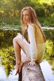 Donna della testarossa che si siede su una corteccia di albero vicino al fiume Immagini Stock