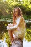 Donna della testarossa che si siede su una corteccia di albero vicino al fiume Immagine Stock Libera da Diritti