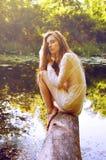 Donna della testarossa che si siede su una corteccia di albero vicino al fiume Fotografia Stock