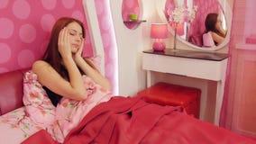 Donna della testarossa nell'emicrania di sofferenza del letto rosa stock footage