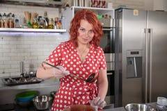Donna della testarossa sulla cucina con una siviera Fotografie Stock Libere da Diritti