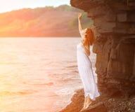 Donna della testarossa in vestito che sta sulla spiaggia fotografia stock libera da diritti
