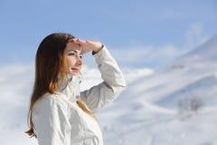 Donna della viandante che guarda in avanti nella montagna nevosa Fotografia Stock