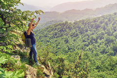 Donna della viandante che la alza armi su sull'alta scogliera Immagine Stock Libera da Diritti