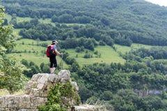 Donna della viandante che sta sull'le rocce in un'alta montagna Fotografia Stock Libera da Diritti
