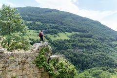 Donna della viandante che sta sull'le rocce in un'alta montagna Fotografia Stock