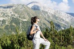 Donna della viandante in un'alta montagna, guardante il panorama Immagine Stock