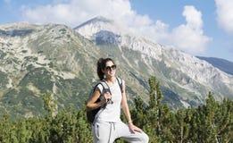 Donna della viandante in un'alta montagna, guardante il panorama Fotografie Stock