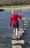 Donna delle pietre facenti un passo che cammina attraverso il fiume Immagine Stock Libera da Diritti