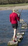 Donna delle pietre facenti un passo che cammina attraverso il fiume Fotografie Stock Libere da Diritti