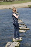 Donna delle pietre facenti un passo che cammina attraverso il fiume Fotografia Stock Libera da Diritti