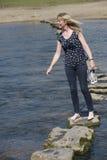 Donna delle pietre facenti un passo che cammina attraverso il fiume Fotografia Stock