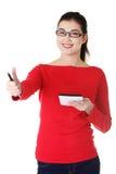 Donna dello studente che per mezzo di una compressa che mostra i pollici su Immagini Stock