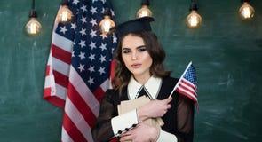 Donna dello studente che tiene la bandiera di U.S.A. Istruzione e concetto della gente - studenti sorridenti con la borsa e carte Fotografia Stock Libera da Diritti