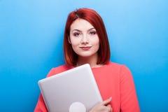 Donna dello studente della testarossa con un computer portatile in mani Fotografie Stock