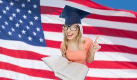 Donna dello studente in tocco con l'enciclopedia Immagine Stock Libera da Diritti