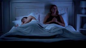Donna deludente che si siede sul letto, ragazzo che dorme, insoddisfatto con vita fotografie stock