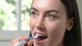 Donna in denti di spazzolatura del bagno con lo spazzolino da denti manuale video d archivio